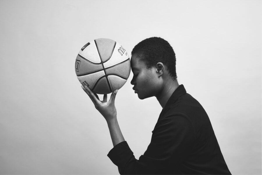 Frau seitlich mit Basketball in linker Hand und Kopf berührt Ball