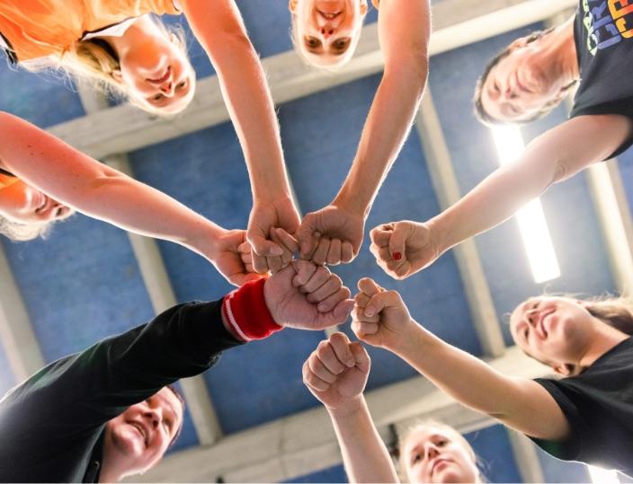 Sportlerinnen strecken Hände in die Mitte MentalWin