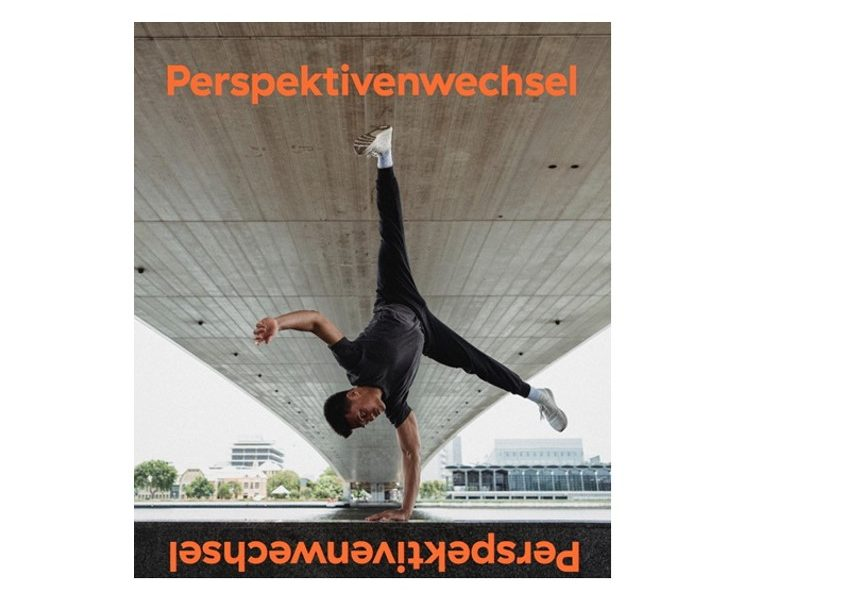 Mann macht Handstand unter Brücke