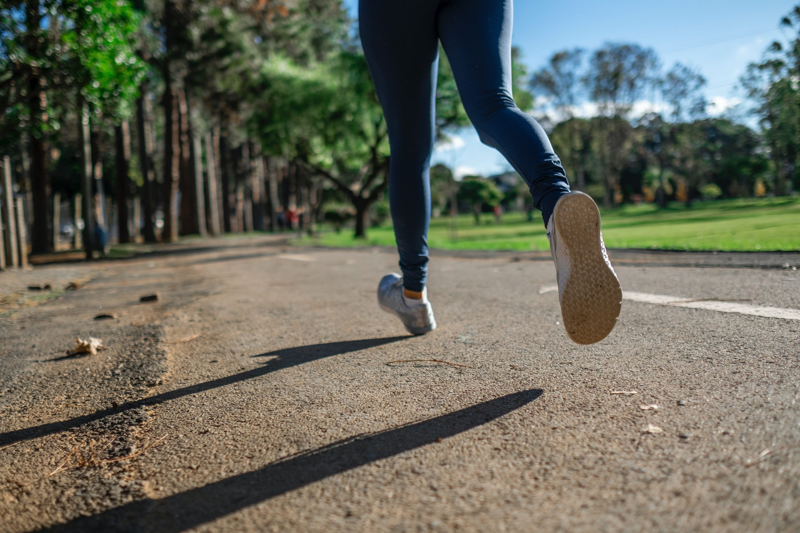 Frau mit Turnschuhen beim Jogging auf Asphaltweg; im Hintergrund sind Bäume und eine Rasenfläche