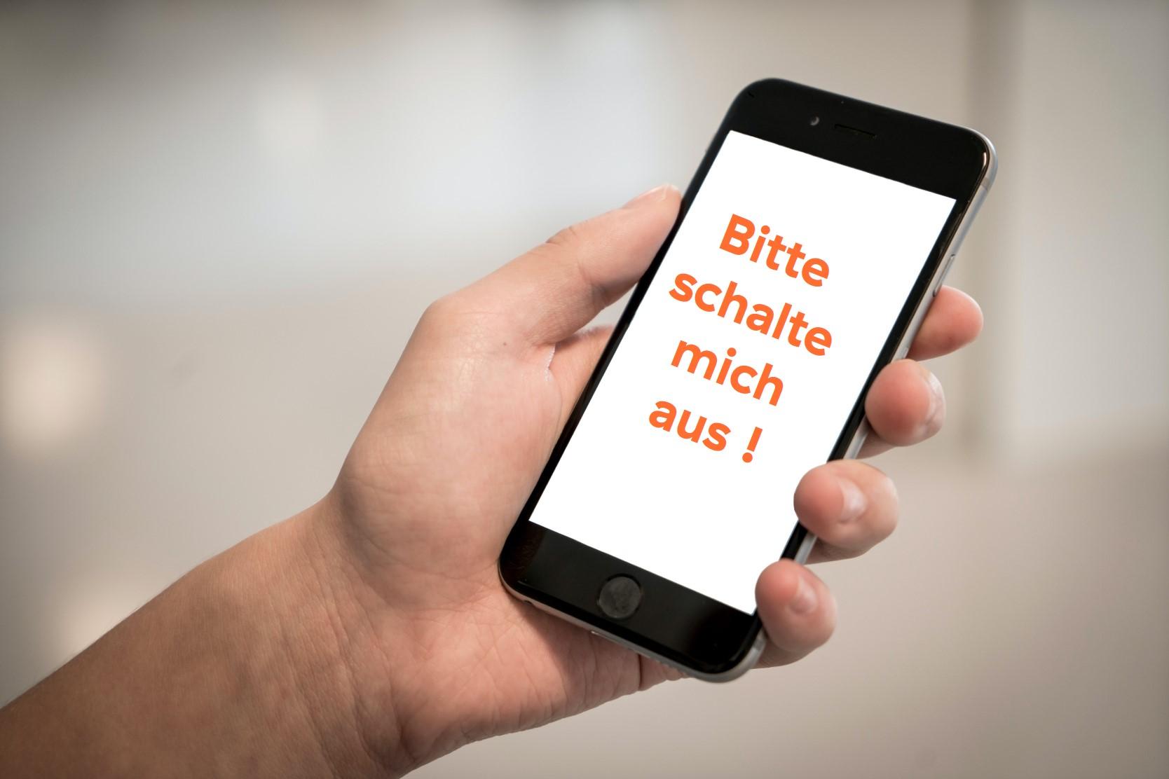 Handy in der linken Hand mit Aufschrift: bitte schalte mich aus
