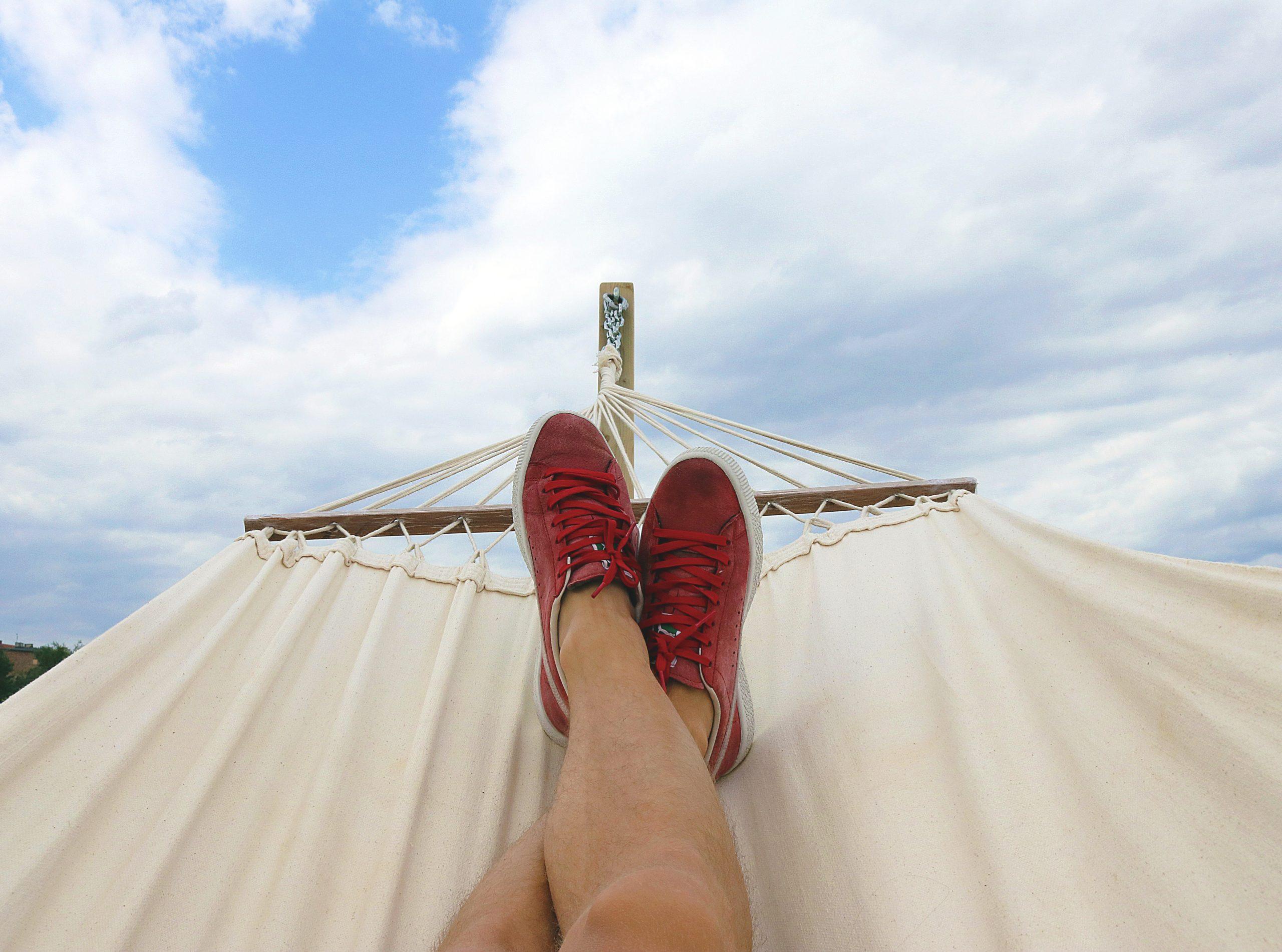 Beine in einer Hängematte, blauer Himmel mit weißen Wolken